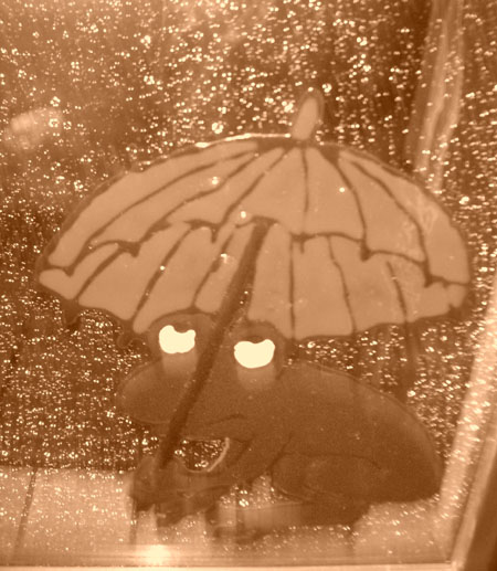 Frosch mit Schirm sitzt im Regen